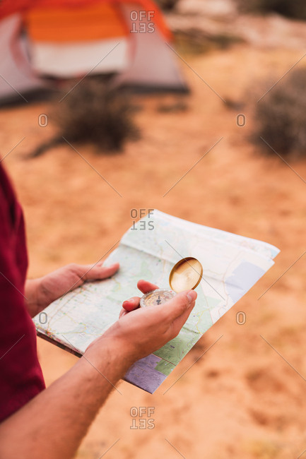 Crop man holding map and retro compass while standing on blurred background of majestic desert