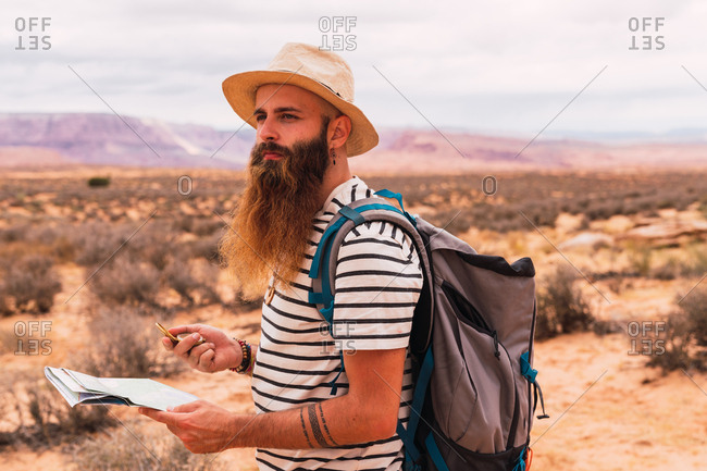 man holding map and retro compass while standing on blurred background of majestic desert