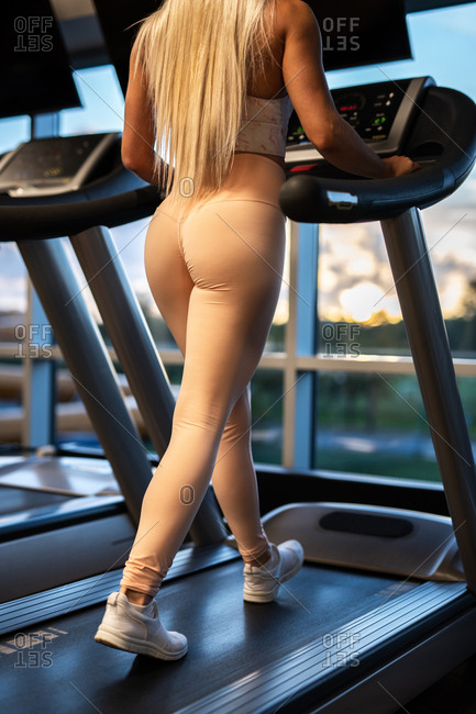 Crop back view of fit sportswoman in sportswear and sneakers doing exercise on treadmill in gym in front of window