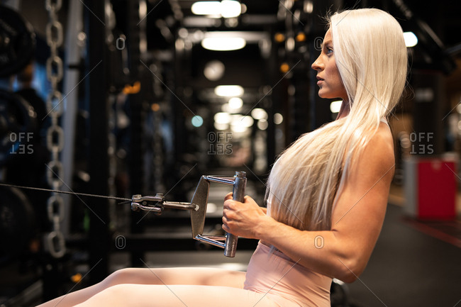 Side view of beautiful blond woman in sportswear doing workout on training equipment in gym
