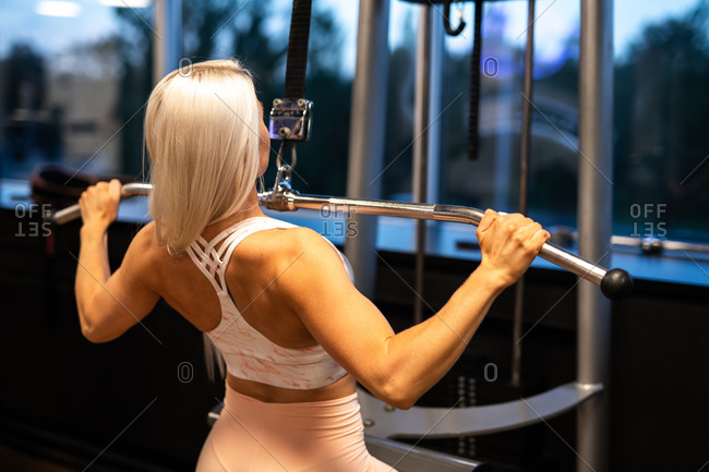 Back view of attractive young woman in sportswear doing Lat Pull Down exercise on gym equipment near window