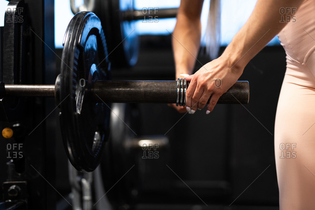 Crop view of woman in sportswear preparing barbell for workout in gym
