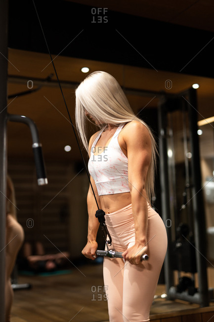 Side view of attractive blond sportswoman in top and tights doing Straight Arm Push down exercise on background of gym equipment