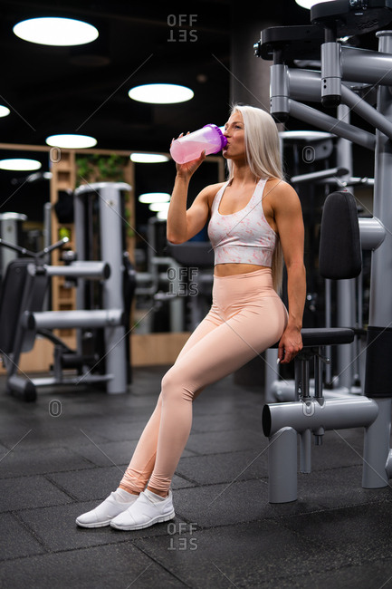 Side view of beautiful blond woman in sportswear and white sneakers sitting on gym equipment and drinking water