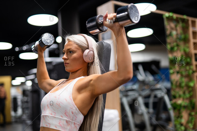 Young blond woman in sport top with headset doing exercise with iron dumbbells on gym equipment