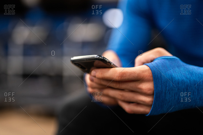 Crop view of hands of man in blue pullover using smartphone on blurred background