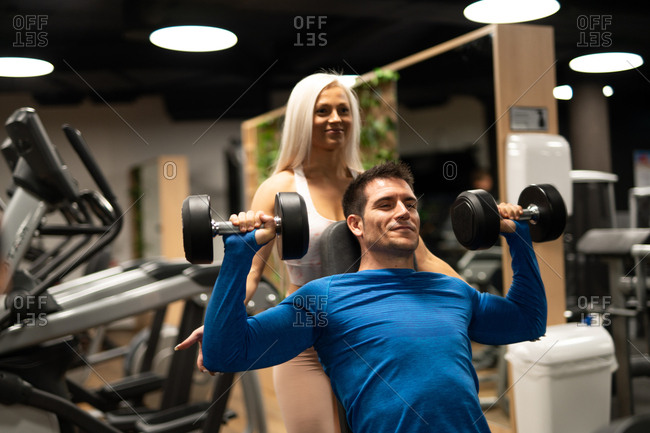 Beautiful woman with blond hair helping man in blue pullover to do exercise with dumbbells in gym