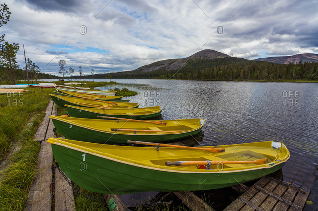 Yellow and green similar boats placed on shore of blue rippling river on background of mountains and cloudy sky