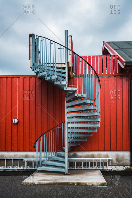 Winding metal staircase leading to house placed behind high red fence on background of cloudy sky