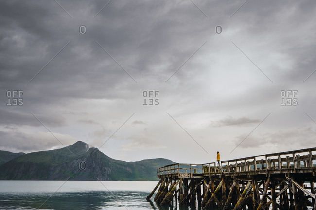 Clean still lake with pier on background of high beautiful mountains and overcast sky