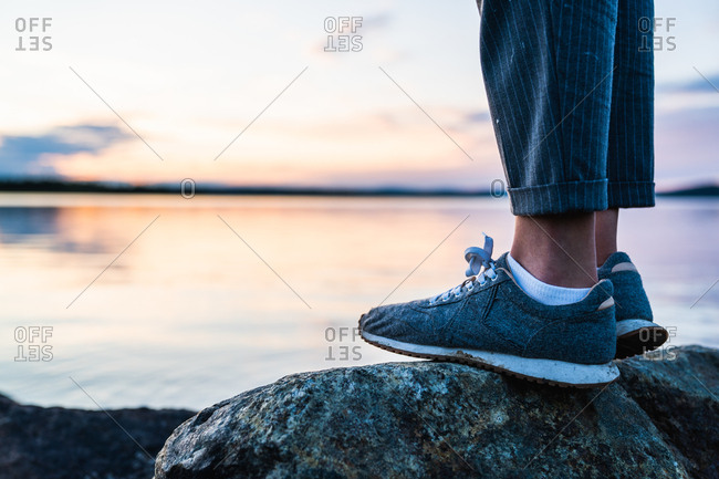 Crop side view of feet of person standing on stone near still lake on background of clear sky