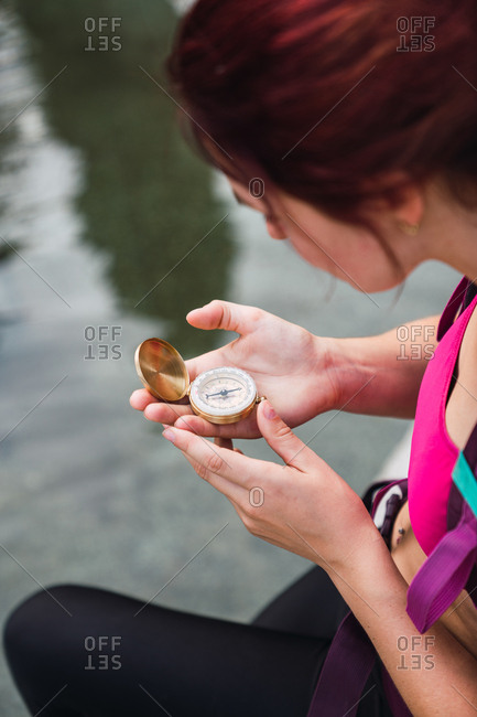 Crop side view of young woman in sportswear sitting near still water with golden compass in hand