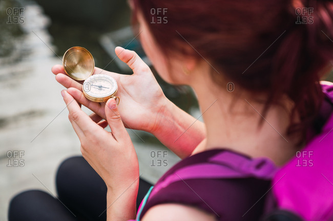 Woman sitting near lake with compass in hand