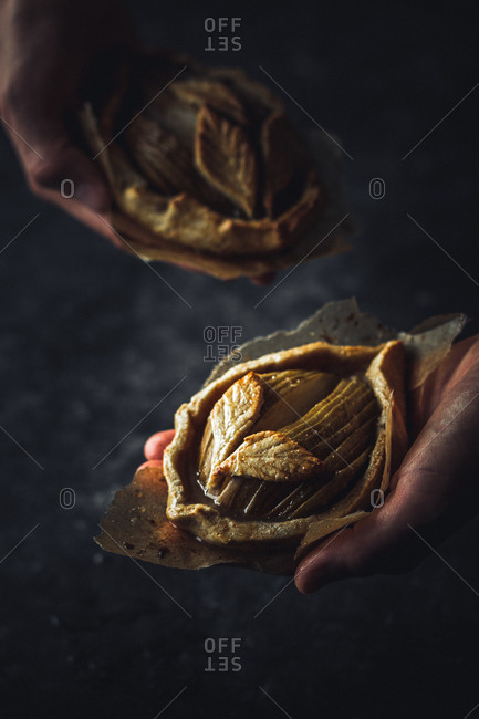 Hands of anonymous person holding leaf-shaped pieces of parchment and palatable fresh buns on dark background