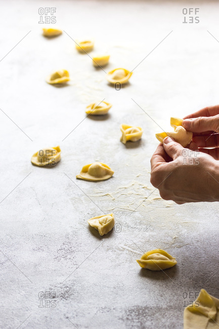 Crop person making natural tortellini
