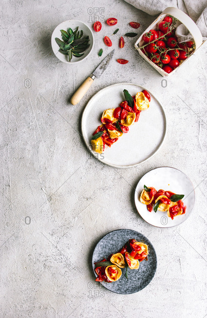 From above shot of plates with boiled stuffed tortellini garnished with herb and tomatoes
