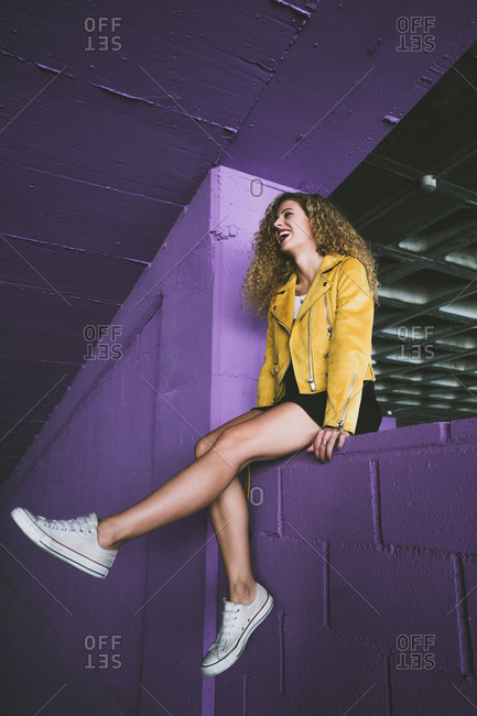 From below side view of stylish curly blonde in sneakers and yellow jacket sitting on purple wall and laughing