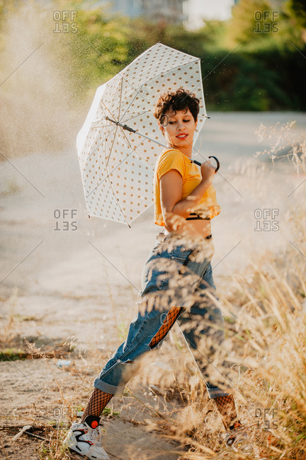 Side view of pretty female in stylish outfit smiling and looking away while walking near asphalt path under drops of spraying water