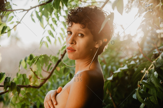 Side view of beautiful sensual brunette with short hair standing in water mist in green vegetation with sunlight