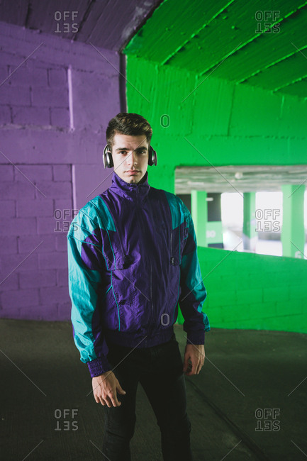 Young handsome man in sport jacket with headset standing on background of colorful wall and looking at camera