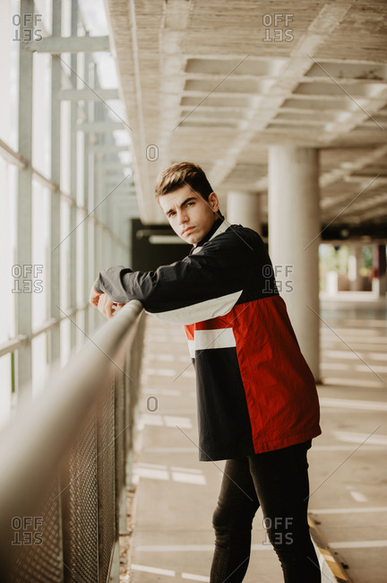 Young thoughtful man standing inside building