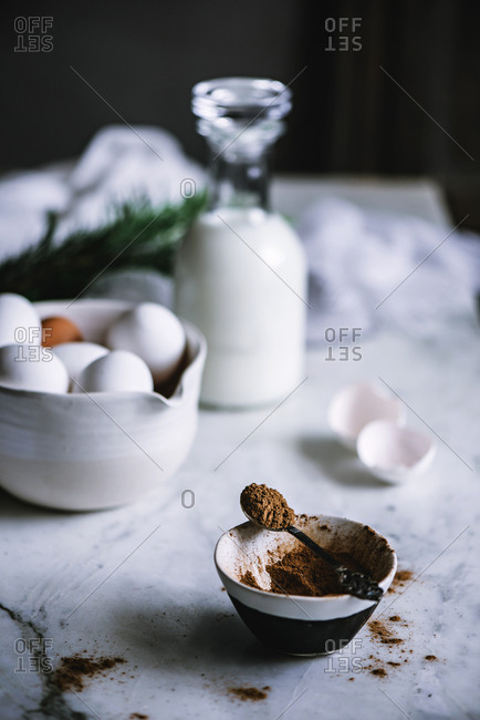 Bowl and spoon of cocoa powder standing on marble tabletop near bowl of fresh eggs and bottle of nice dairy