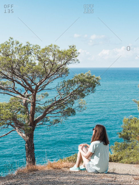 Woman sitting on cliff of blue seaside