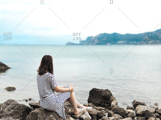 Back view of woman in striped dress sitting alone on rocks of seashore looking away in dreams