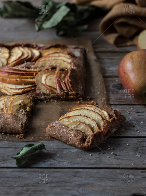Dead leaf and ripe apple lying near palatable pie on wooden tabletop