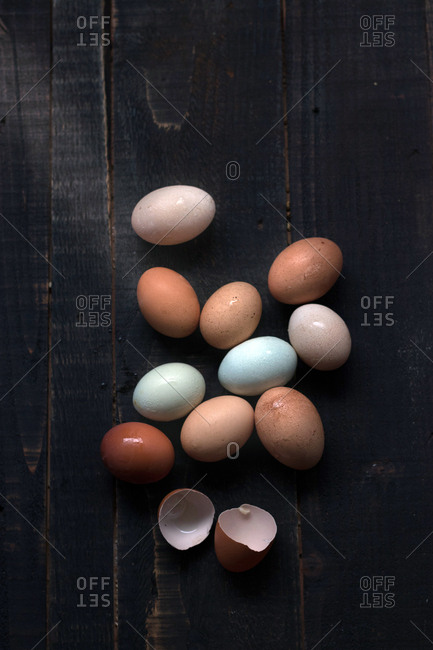 From above shot of eggs on wooden table with eggshell near
