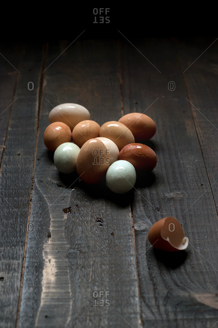 Closeup of pile of white and brown eggs with wet shell composed on wooden table