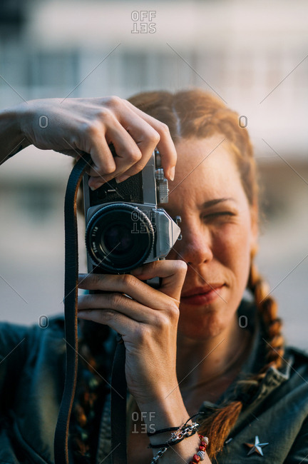 Pretty redhead girl with braids taking pictures. It is in the city of Madrid Spain.
