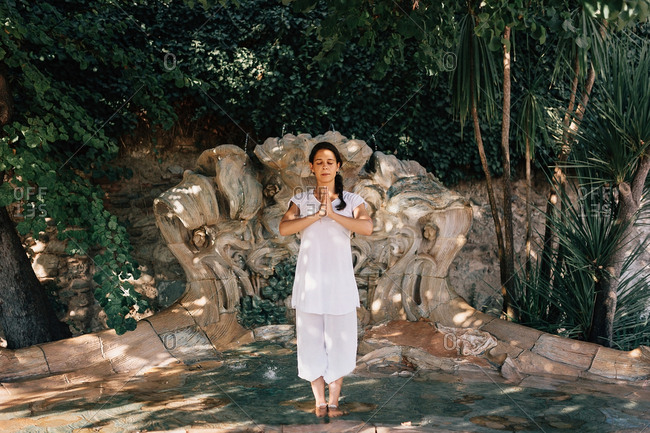 Beautiful female keeping eyes closed and standing in fountain water in Tree pose while doing yoga in park
