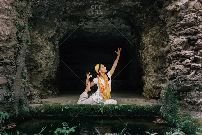 Barefoot female keeping eyes closed and meditating while sitting in lotus pose near stone cave