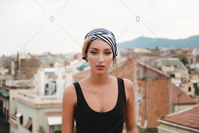 Beautiful woman in kerchief on head and black top standing on rooftop and looking at camera on background of city