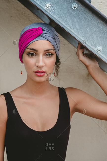 Woman in headscarf standing near ladder