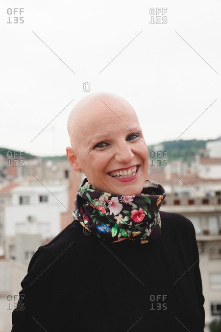Bald smiling woman with bright makeup in black coat standing on rooftop and looking at camera on background of cityscape