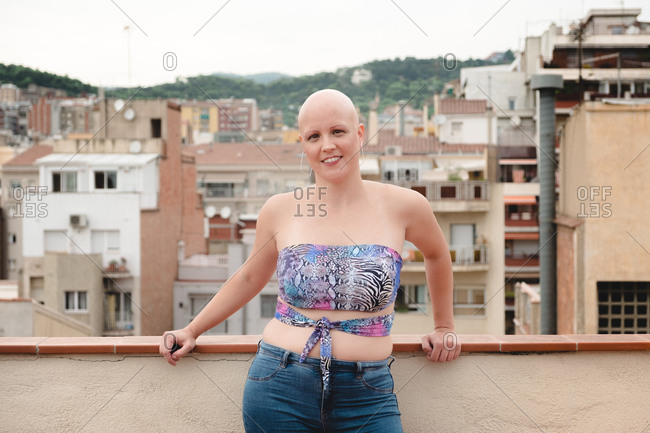 Bald woman in summer top and jeans standing on rooftop and looking at camera on background of town