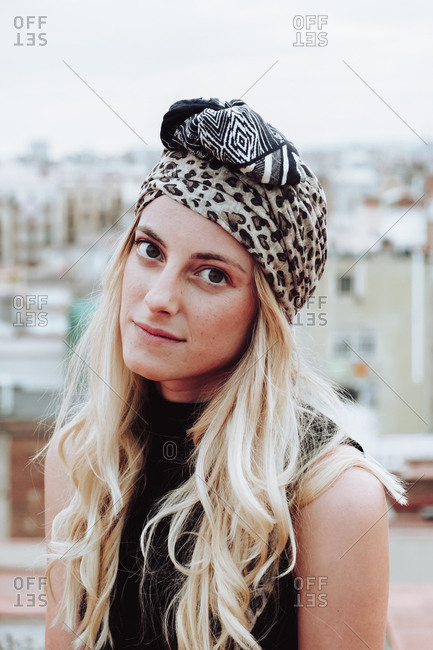 Young attractive woman with blond hair in patterned head cloth sitting on rooftop and looking at camera on background of cityscape