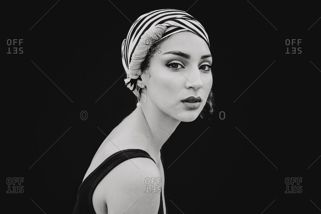 Side view of beautiful young woman in striped head cloth with bright makeup looking at camera isolated on black background