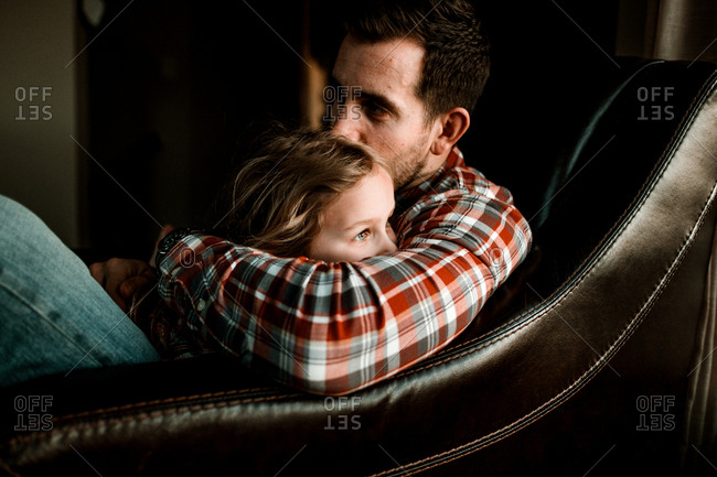 Daughter and Dad snuggling in an armchair