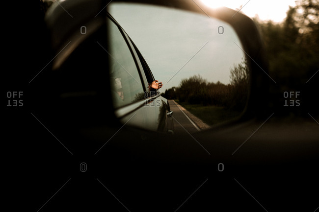 Girl waving out of car window