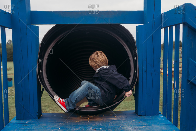 Child sitting at top of tube slide on playground