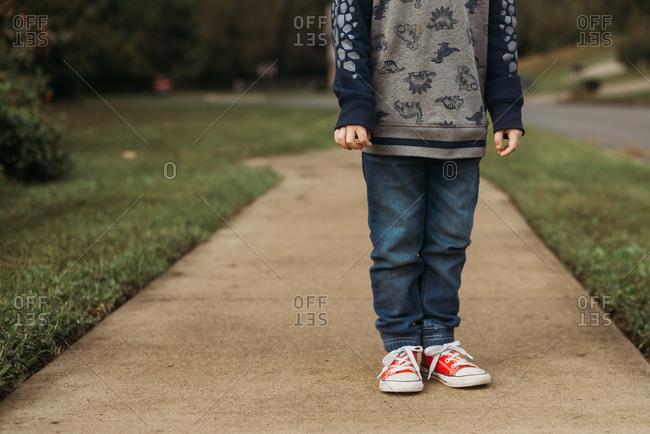 Child standing on the sidewalk