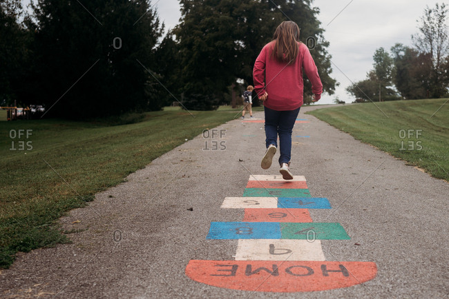 Girl jumping on one foot while playing hopscotch
