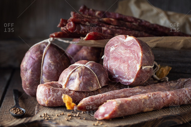 Delicacy smoked meat and sausages over wooden surface