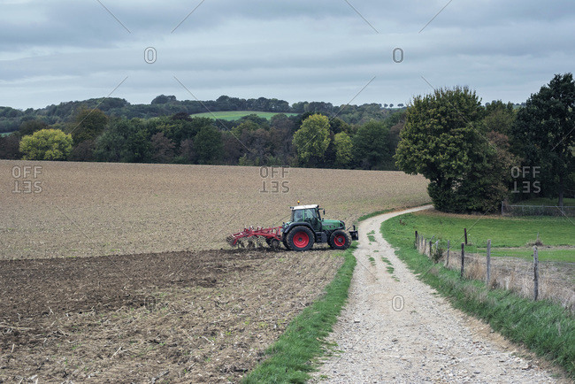 Rural farmland with tractor along gravel road
