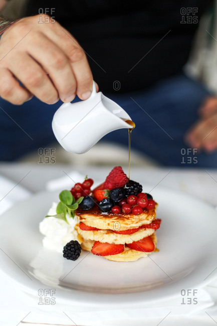 Person pouring syrup over berry pancakes served with whipped cream