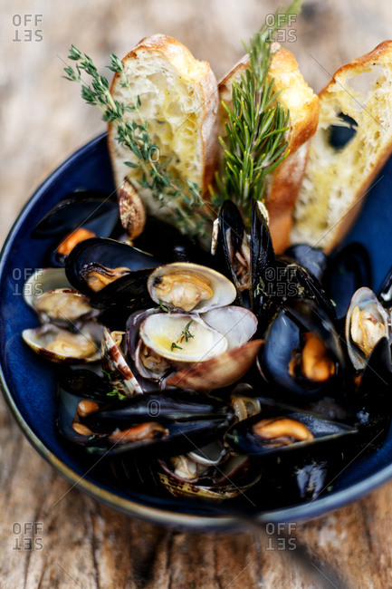 Dish with freshly cooked mussels served with bread and sprig of rosemary