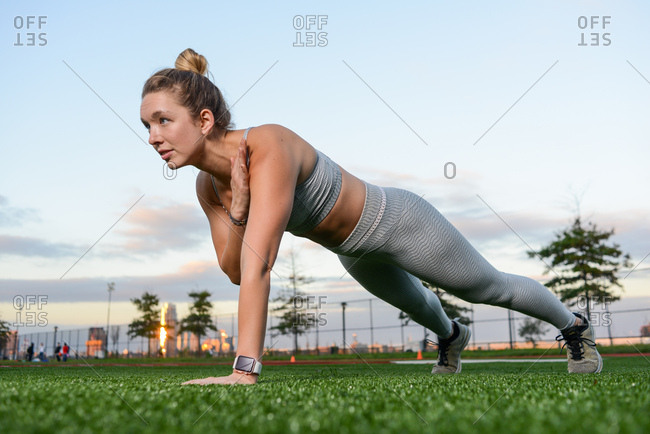 Woman doing pushups in city park